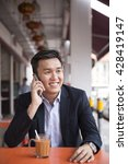 Small photo of Chinese business man drinking a cup of coffee while sitting with his phone in an Asian food court or Hawker centre cafe.