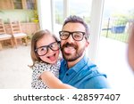 Small photo of Father with his little daughter sticking tongue out