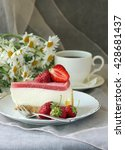 Small photo of A piece of cake, white cup of tea and strawberries.