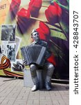 Small photo of VOLGOGRAD, RUSSIA - May 04, 2016: A live sculpture of the Soviet soldier of the player on an accordion against a card with flowers. Volgograd, Russia
