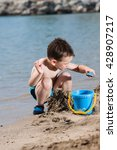 Little Boy In Blue Sea Playing...
