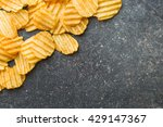Small photo of Crinkle cut potato chips on table. Tasty spicy potato chips.