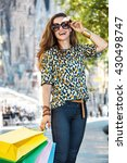 Small photo of Getting unique trends of Barcelona. Full length portrait of smiling fashion-monger woman with shopping bags standing on the street