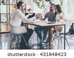 Small photo of Good news for you! Cheerful young couple bonding to each other and listening to their financial advisor sitting at the desk in front of them