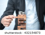 Small photo of Planning, risk and strategy in business, businessman gambling placing wooden block on a tower