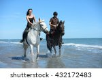 Stock photo happy young couple vacation riding horses on the beach in a sunny summer day 432172483