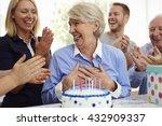 Senior Woman Blows Out Birthda...