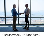 Small photo of Full length shot of two businessmen shaking hands to acknowledge their partnership, and smiling positively, with a large office window behind them