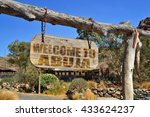 "Small photo of old vintage wood signboard with text "" welcome to Abuja"" hanging on a branch"