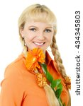 Small photo of blond hair and blue eyes girl in orange blouse holds flower african daisy