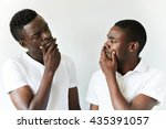 Small photo of Portrait of two cautious and thoughtful black guys wearing white T-shirts looking at each other with skeptical and suspicious expression, holding hands on chin. Human face expressions and emotions