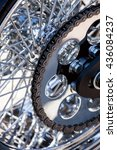 Small photo of motorcycle chain on a back wheel with chromic spokes.