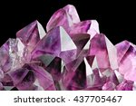Crystal Stone macro mineral, purple rough amethyst quartz crystals on black background