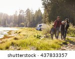 Stock photo family on a camping trip walking near a lake 437833357