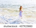 Small photo of beautiful blonde teenage girl wearing flowy white dress standing ankle dee in ocean water