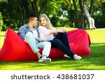 young couple seated on a couch... | Shutterstock . vector #438681037