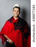 Small photo of smiling albanian fan covered with albanian flag in front of grey background