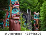 Detail of totem pole at Saxman Village tribal house near Ketchikan Alaska with Sun Raven in background