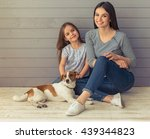 Stock photo cute little daughter and her beautiful young mother are looking at camera and smiling while posing 439344823
