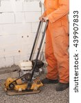 Small photo of builder with vibratory plates seals the base for pouring concrete