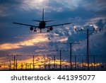 Small photo of Airplane landing into the sunset