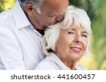 Small photo of Close-up portrait of an elder marriage in natural surrounding, the man affectionately kissing his wife's head