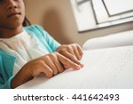 girl using braille to read at...
