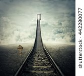 Small photo of Railroad of opportunity along a cracked desert ground, going up as a staircase to a opened door in the sky, road to heaven symbol. Success plan, business concept