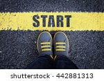Small photo of Start line child in sneakers standing next to a yellow starting line