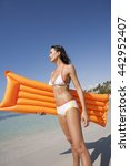 Small photo of woman on a heavenly beach with an orange air mattress