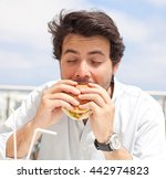 young man eating a hamburger | Shutterstock . vector #442974823