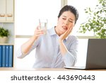 Small photo of Young asian business woman with tooth sensitivity in office