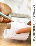 Small photo of Closeup of female accountant working by checking a printout or receipt coming out of adding machine looking at numbers holding a pen.