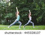Two Women Practicing Yoga In...