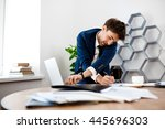 Small photo of Absentminded young businessman speaking on phone, office background.