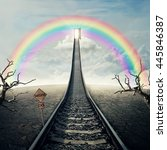 Small photo of Railway of opportunity along a cracked desert ground with dry trees, going up as a staircase to a opened door over the rainbow in the sky. Road to success symbol. Business planning concept
