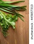 Small photo of Onion Allium nutans and salad on wooden background