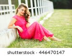 Stock photo beautiful young woman girl sitting on a green grass near the white fence wearing long pink dress 446470147