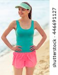 Small photo of Beautiful girl in sport clothes is looking away and smiling while standing akimbo on the beach
