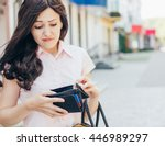 Stock photo unhappy bankrupt woman with empty wallet young woman shows her empty wallet bankruptcy 446989297