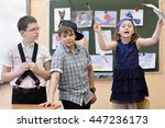 Small photo of three students: two boys and one girl act out scene in class performance at drawing lesson