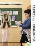 Small photo of Two student act out scene in class performance at drawing lesson, focus on left girl