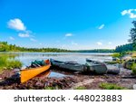 Small photo of Three canoes on the shore of a lake in the Boundary Waters Canoe Area in the North Woods of Northern Minnesota wait for the paddlers to return from a portage.