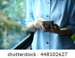 woman holding smartphone with... | Shutterstock . vector #448102627