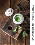 Small photo of Vintage ceramic bowl with broccoli mashed and aioli sauce, served with sackcloth rag on wood chopping board over old wooden background. Rustic style. Flat lay
