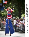 Small photo of NEW YORK - JUNE 12 2016: A woman dressed in the red, white, and blue pattern of the Puerto Rican flag walks on stilts in the 59th National Puerto Rican Day Parade on 5th Ave in NYC on June 12 2016.