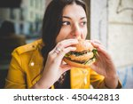 young woman sitting  eating an... | Shutterstock . vector #450442813