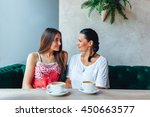 two happy women talking in cafe.... | Shutterstock . vector #450663577