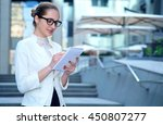 woman in glasses takes notes.... | Shutterstock . vector #450807277