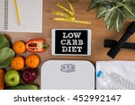 Small photo of LOW CARB DIET top view, digital tablet on a wooden table, fitness and weight loss concept, dumbbells, white scale, towels, fruit, Weight loss